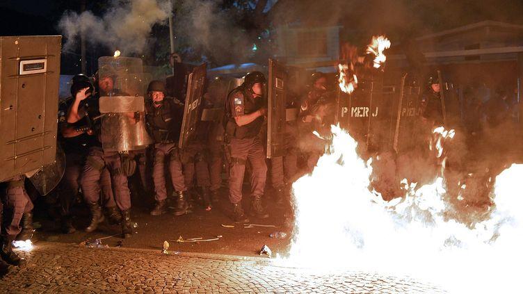 Des policiers faisant face aux manifestants antigouvernement, à Rio de Janeiro (Brésil), le 22 juillet 2013. (YASUYOSHI CHIBA / AFP)