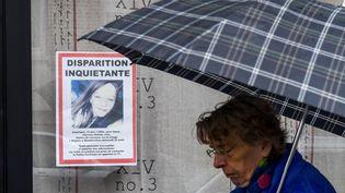 Une femme passe devant un avis de disparition de la jeune Angélique àWambrechies (Nord), le 29 avril 2018. (PHILIPPE HUGUEN / AFP)