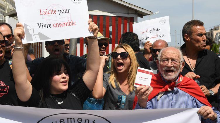 """Une Tunisienne affiche une pancarte sur laquelle on peut lire : """"Laïcité pour vivre ensemble"""" lors d'une manifestation en mai 2018pour dénoncer la fermeture des cafés et des restaurants pendant le mois de ramadan. (FETHI BELAID / AFP)"""