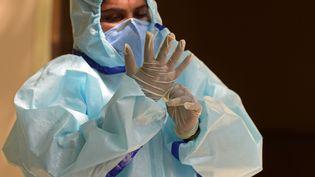 Unesoignante vêtue d'un équipement de protection individuel (EPI) ajuste ses gants dans un centre de dépistage du Covid-19 en Inde, le 21 juillet 2020. (NOAH SEELAM / AFP)