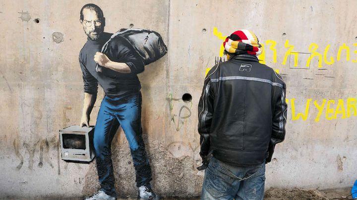 "L'oeuvre de Banksy montrant Steve Jobs et légendée ""The son of a migrant from Syria"".  (Banksy.co.uk)"