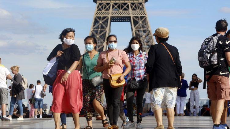 Des personnes portent un masque devant la tour Eiffel, le 2 août 2020. (MEHDI TAAMALLAH / NURPHOTO / AFP)