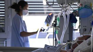 Une soignante prend en charge en soins intensifs un patient à Mulhouse (Haut-Rhin), le 23 juillet 2021. (SEBASTIEN BOZON / AFP)