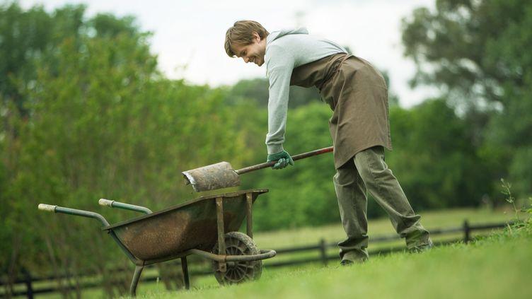 Un jardinier verse une pelletée de terre dans une brouette. (MAXPPP)