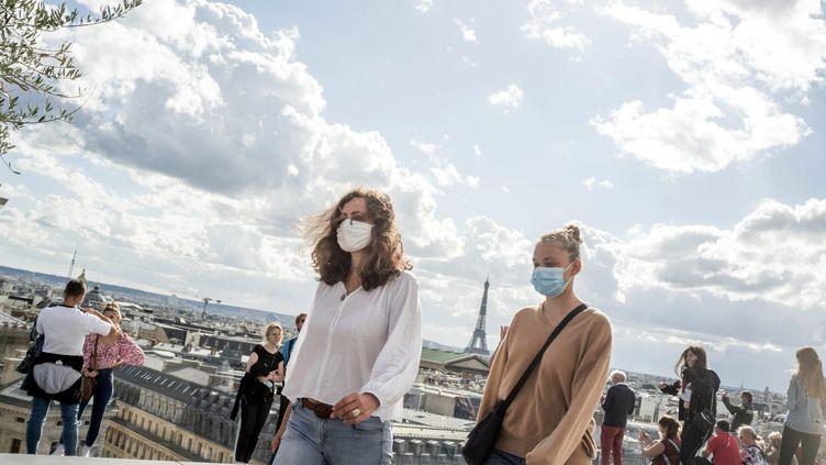 Deux passantes portant le masque sanitaire à Paris. (BRUNO LEVESQUE / MAXPPP)