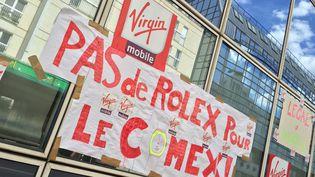 Une affiche placardée le 22 juillet 2015 sur la façade du siège de Virgin Mobile,à Levallois-Perret (Hauts-de-Seine), par les salariés de l'entreprise qui exigent le remboursement de primes accordées aux dirigeants. (CHRISTOPHE RAUZY / FRANCETV INFO)