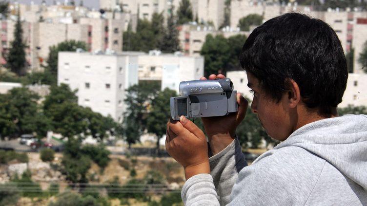 Un jeune Palestinien utilise une caméra, distribuée par l'ONGB'Tselem à sa famille, en 2008 près d'Hébron en Cisjordanie. (HAZEM BADER / AFP)