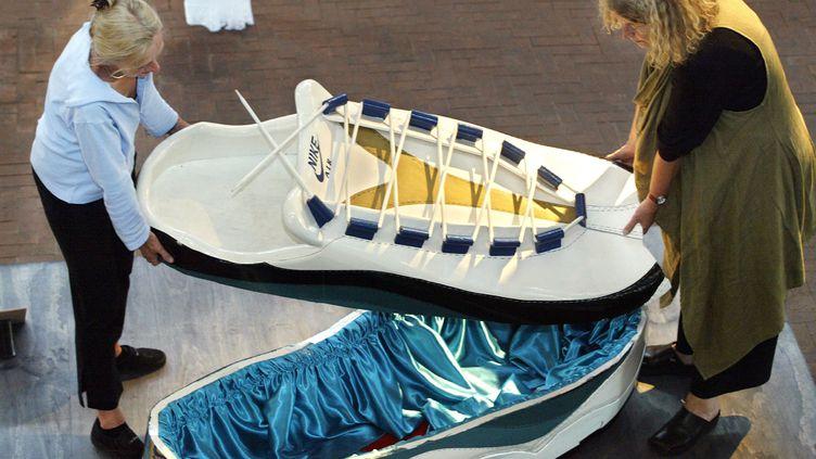 Une collectionneuse hollandaise (à gauche) présente en 2003 à Osnabrück (Allemagne) un modèle de cercueil basket créé par l'artiste Paa Joe du Ghana. (DAVID HECKER / DDP)