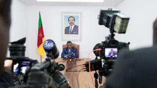 Assis en dessous d'un portrait du président Paul Biya, le Premier ministre camerounaisJoseph Dion Ngute répond aux questions de l'AFP le 3 octobre 2019 à Yaoundé, la capitale politique du Cameroun. (STRINGER / AFP)