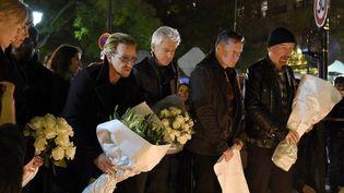 Les membres de U2 Bono, Adam Clayton, Larry Mullen Jr and The Edge se recueillent devant le Bataclan, samedi 14 novembre en fin d'après-midi  (FRANCK FIFE / AFP)