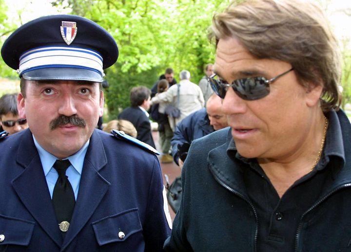 """Sous la protection d'un policier, il se rend, le 12 avril 2003 à Cognac, à la projection, du téléfilm """"Commissaire Valence"""",dans le cadre du 21e festival du film policier. (PATRICK BERNARD / AFP)"""