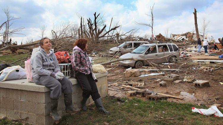 Deux femmes se reposent au milieu des décombres laissés par les tornades, à Henryville dans l'Indiana (Etats-Unis), le 4 mars 2012. (SCOTT OLSON / GETTY IMAGES NORTH AMERICA)