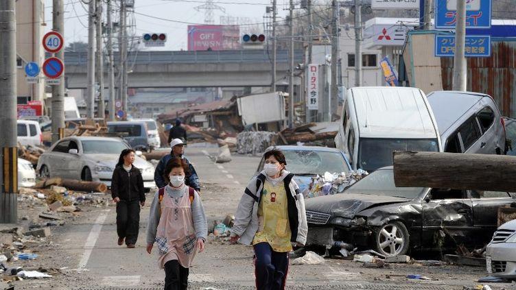 Des habitants dans les ruesd'Ofunato (Japon) dévastées par le tsunami, le 14 mars 2011. (TOSHIFUMI KITAMURA / AFP)