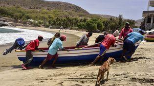 Des pêcheurs ramènent leur bateau sur la plage de Tarrafal, au nord de l'île de Santiago, au Cap-Vert, le 14 avril 2021. (SEYLLOU / AFP)