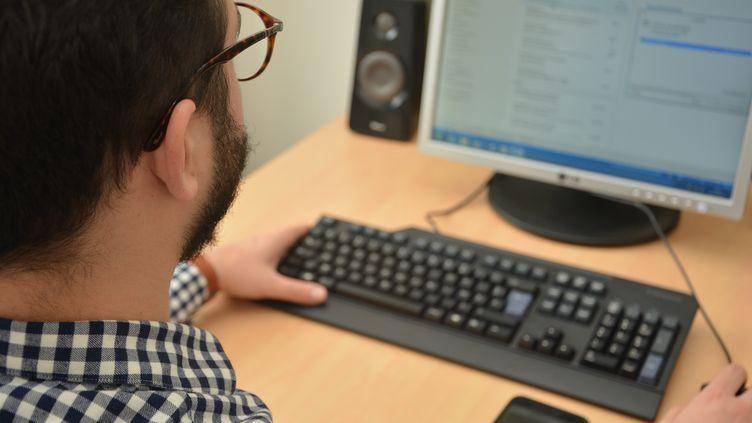 Un homme consulte son ordinateur. (JEAN-CHRISTOPHE BOURDILLAT / RADIO FRANCE)
