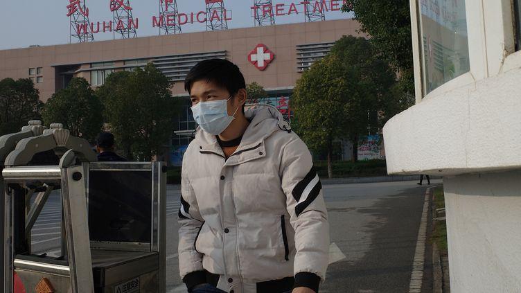 Un homme quitte un centre médical de Wuhan (Chine), le 12 janvier 2020, où est hospitalisé une personne morte des suites d'un premier cas de pneumonie chinoise. (NOEL CELIS / AFP)