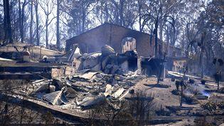 De la fumée s'échappe d'une maison incendiée àTathra (Australie), le 19 mars 2018. (STRINGER / REUTERS)