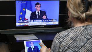 Une femme regarde la conférence de presse de François Fillon à la télévision, le lundi 6 février 2017. (JEAN-FRANCOIS FREY / MAXPPP)