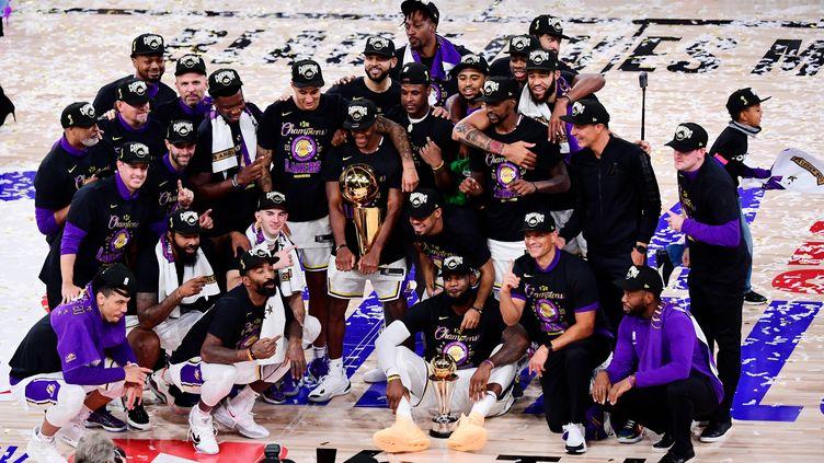 Les Lakers de Los Angeles posent pour une photo d'équipe avec le trophée après avoir remporté le championnat NBA contre Miami, le 11 octobre, à Lake Buena Vista, Floride.  (DOUGLAS P. DEFELICE / GETTY IMAGES NORTH AMERICA)