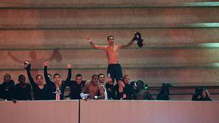 L'attaquant du PSG Angel Di Maria (à droite) debout sur la rambarde du Parc des Princes, fête la qualification de son club en quarts de finale de la Ligue des champions (victoire en 8e contre Dortmund 2-0, 1-2) avec le public, massé à l'extérieur du stade en raison de l'épidémie de coronavirus. (FRANCK FIFE / AFP)