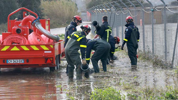 Des pompiers pompent l'eau à l'aéroport d'Ajaccio. (JEAN-PIERRE BELZIT / MAXPPP)