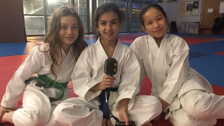 Joséphine, Camille et Yu pratiquent le karaté au centre sportif Jean Talbot, à Paris. (INGRID POHU / RADIO FRANCE)