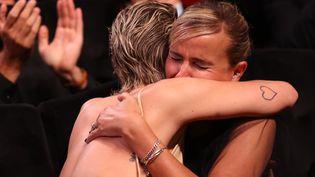 """La rélisatrice française Julia Ducournau embrasse son actrice Agathe Rousselle au moment où elle reçoit la Palme d'OrduFestival de Cannes pour """"Titane"""", le 17 juillet 2021. (VALERY HACHE / AFP)"""