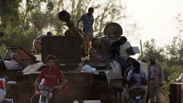 Des combattants de l'opposition syrienne juchés sur un char après la prise de la garnison loyaliste de la Brigade 52, près de Deraa le 9 juin 2015. (Ibrahim Hariri/Anadolu Agency)