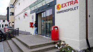 Des fleurs déposées devant le magasin où cinq personnes ont été tuées à Kongsberg (Norvège), cinq jours après l'attaque perpétrée le 13octobre 2021. (TERJE BENDIKSBY / NTB / AFP)
