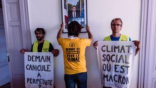Une opération de décrochage du portrait d'Emmanuel Macron par des militants d'ANV-COP21, dans la mairie de Lingolsheim (Bas-Rhin), le 29 juillet 2019. (CHRISTOPH DE BARRY / HANS LUCAS / AFP)
