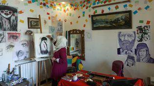 L'artiste syrienne Amani al-Ali travaille sur une peinture dans son appartement d'Idlib. (OMAR HAJ KADOUR / AFP)