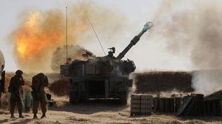 Des soldats israéliens tirent un obus vers la bande de Gaza, le 12 mai 2021, depuis leur position près de Sderot (Israël). (MENAHEM KAHANA / AFP)