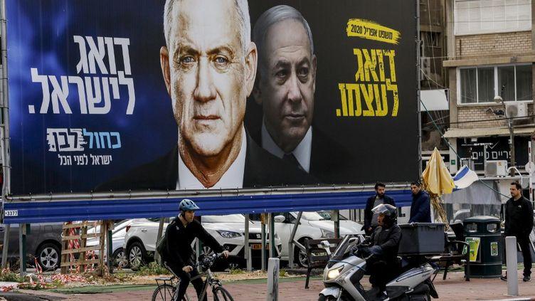 Une affiche représentant Benny Gantz (à gauche) et Benyamin Nétanyahou à Tel Aviv (Israël), lors de la campagne pour les élections législatives, le 1er mars 2020. (MENAHEM KAHANA / AFP)
