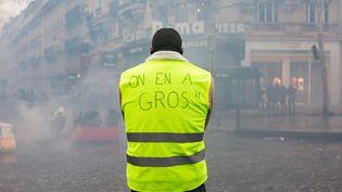 """Au-delà du mot d'ordre initial, dénoncer la hausse des prix du carburant, de nombreux """"gilets jaunes"""" expriment un malaise diffus qui rassemble une colère contre la fiscalité et un sentiment de déclassement social. """"On en a gros"""", affiche cet homme sur les Champs-Elysées, le 24 novembre 2018 à Paris. (EMERIC FOHLEN / NURPHOTO / AFP)"""