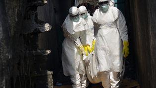 Des membres de la Croix-Rouge en tenue de protection déplacent le corps d'une personne morte d'Ebola, à Monrovia (Liberia), le 5 janvier 2015. (ZOOM DOSSO / AFP)