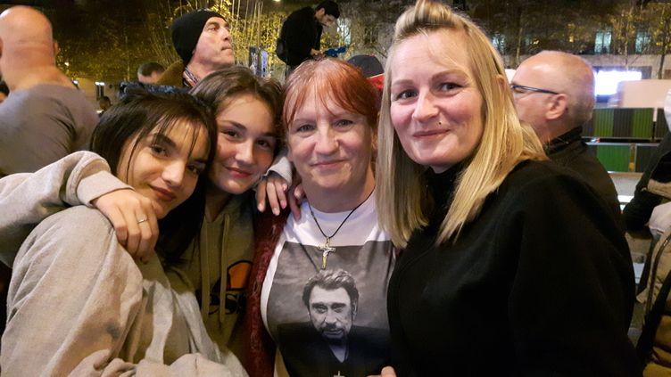 Christine (centre) est venue en famille à la Fnac des Champs-Elysées,exceptionnellement ouverte dans la nuit du 19 octobre, pour être l'une des premières à écouter le nouvelet dernier album de son idole Johnny Hallyday. (ALICE SERRANO / RADIO FRANCE)