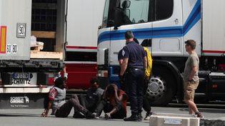 La police interpelle des migrants dans un camion sur le parking d'une station service, à Calais (Pas-de-Calais). (OLIVIER ARANDEL / MAXPPP)