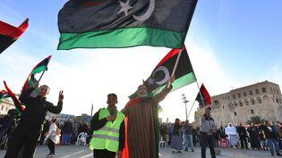 Des habitants agitent des drapeaux de la Libye lors d'une manifestation contre les attaques et les violations du cessez-le-feu des troupes du général Khalifa Haftar, à Tripoli, en Libye, le 24 janvier 2020. (HAZEM TURKIA / ANADOLU AGENCY / AFP)