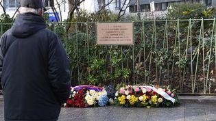 Un passant se recueille devant la plaque en mémoire du policierAhmed Merabet, à Paris le 5 janvier 2017. (ERIC FEFERBERG / AFP)