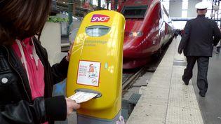 Une femme composte un billet de train le 3 mai 2013, à Lille. (DENIS CHARLET / AFP)