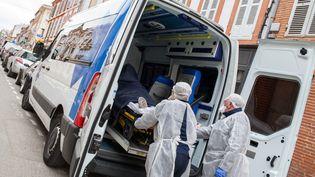 Des ambulanciers prennent en charge un cas présumé de Covid-19 dans le centre de Montauban le 6 avril 2020. (PATRICIA HUCHOT-BOISSIER / HANS LUCAS)
