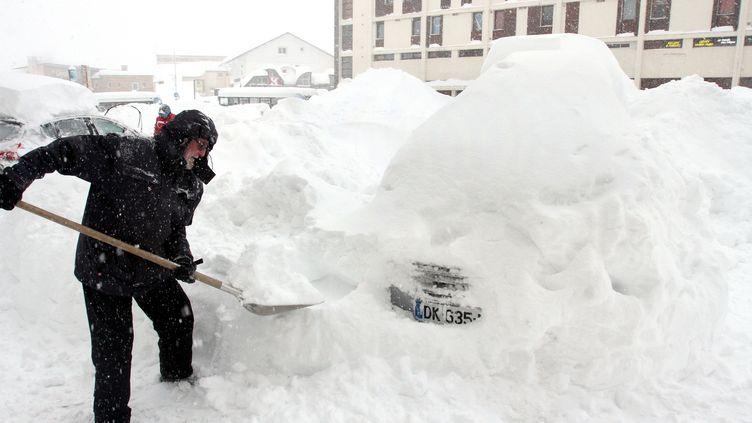 Un homme déblaye la neige entassée sur son véhicule, à Saint-Lary-Soulan(Hautes-Pyrénées), le 1er février 2015. (LAURENT DARD / AFP)