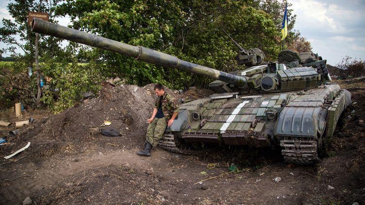 Un soldat ukrainien et son tank, dans l'est de l'Ukraine, près de Donetsk,le 25 août 2014. (OLEKSANDR RATUSHNIAK / AFP)