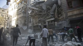 Des Syriens se regroupent autour d'un bâtiment touché parles bombardements, à Alep le 27 septembre 2016. (KARAM AL-MASRI / AFP)