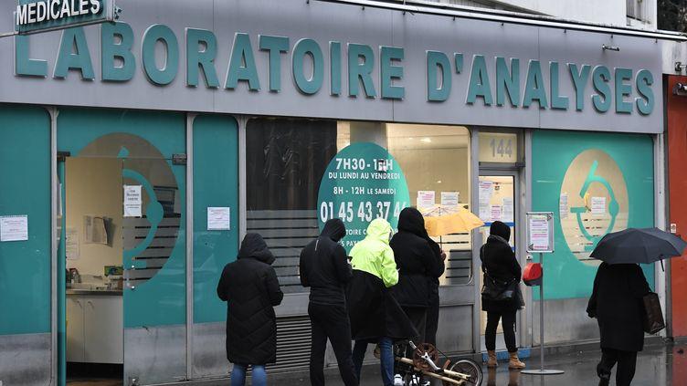 La file d'attente devant un laboratoire d'analyses médicales à Paris, le 22 décembre 2020. (STEPHANE DE SAKUTIN / AFP)