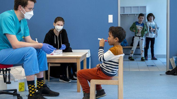 """Une équipe médicale suitun garçon d'âge préscolaire qui utilise un nouveau test Covid-19 en forme de sucette avant de tester des enfants d'âge préscolaire au """"City of Vienna Kindergarten"""" à Vienne, en Autriche, le 28 avril 2021. (JOE KLAMAR / AFP)"""