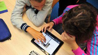 Des élèves utilisent une tablette numérique en classe, au collège Léonard de Vinci, à Saint-Brieuc (Côtes-d'Armor), le 12 septembre 2013. (  MAXPPP)