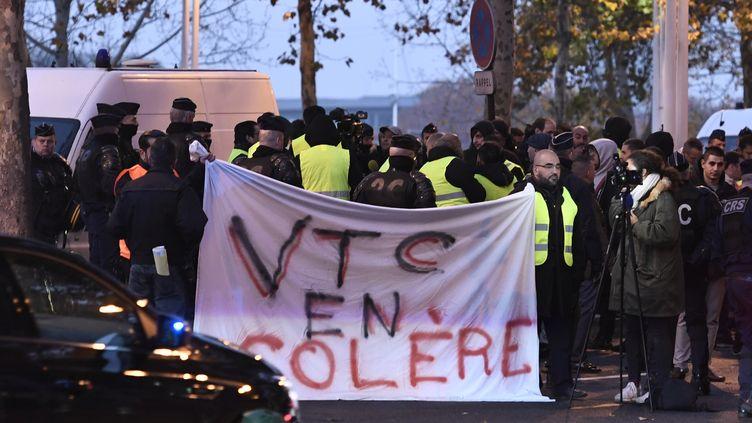 """Protestation des VTC pendant une manifestation des """"gilets jaunes"""", le 17 novembre 2018 près du ministère des Finances à Paris. (STEPHANE DE SAKUTIN / AFP)"""