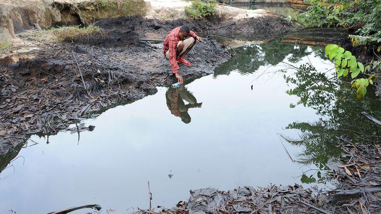 Dans cette photo d'archives prise le 11 août 2011, un homme écope du pétrole brut qui proviendrait d'une panne d'équipement Shell dans l'Ogoni, dans l'État de Rivers, au sud du Nigeria. (PIUS UTOMI EKPEI / AFP)