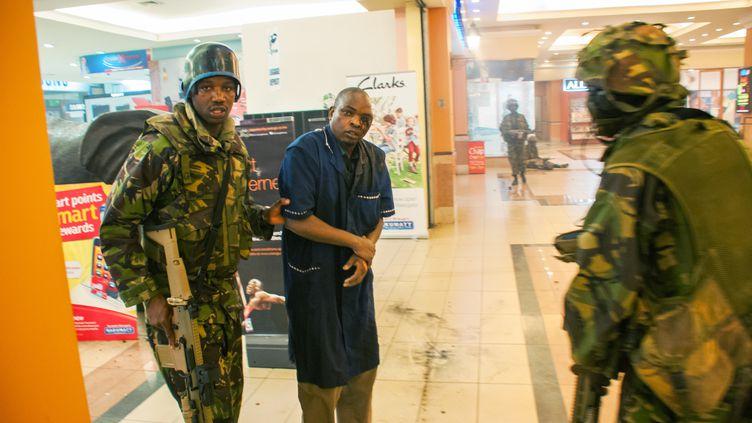 Un Kényan secouru par des forces spéciales de l'armée, samedi 21 septembre 2013, à Nairobi, au Kenya. (JAMES QUEST / AFP)